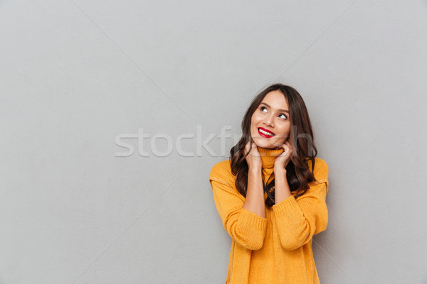 Image of Happy brunette woman in sweater looking up Stock photo © deandrobot