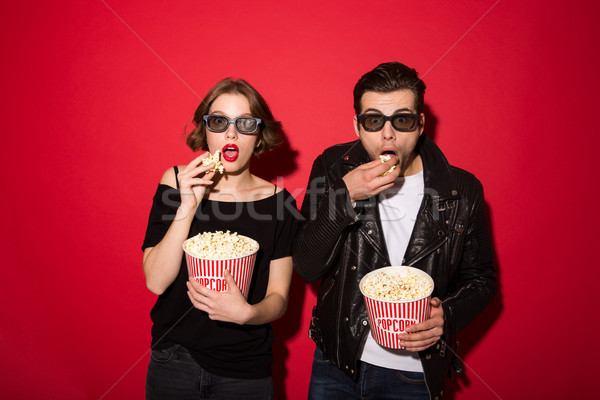 Surprised punk couple eating popcorn and looking at the camera Stock photo © deandrobot