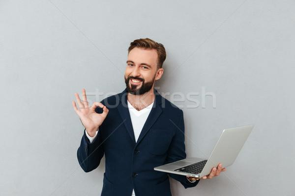 Jovem barbudo homem terno olhando câmera Foto stock © deandrobot