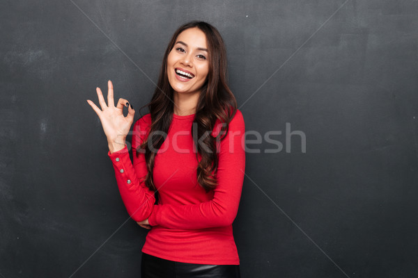 Happy brunette woman in red blouse showing ok sign Stock photo © deandrobot