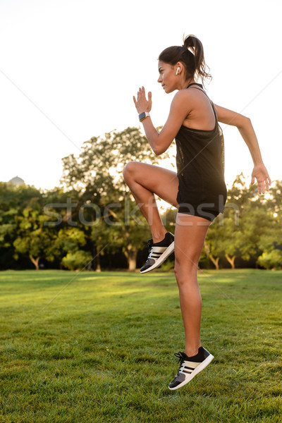 Side view portrait of a fitness woman in earphones Stock photo © deandrobot