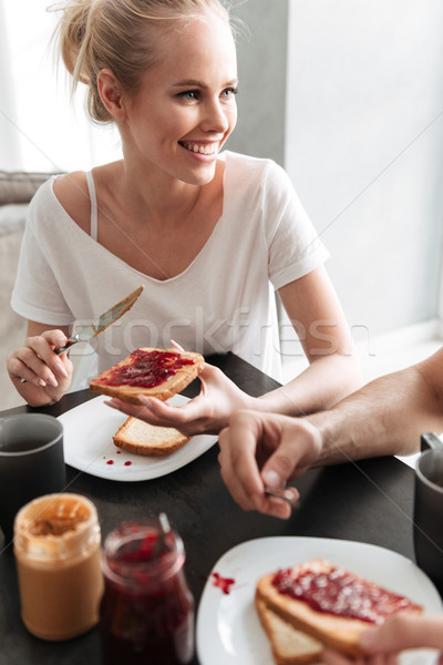 Smiling blonde woman talking and put jam on bread Stock photo © deandrobot