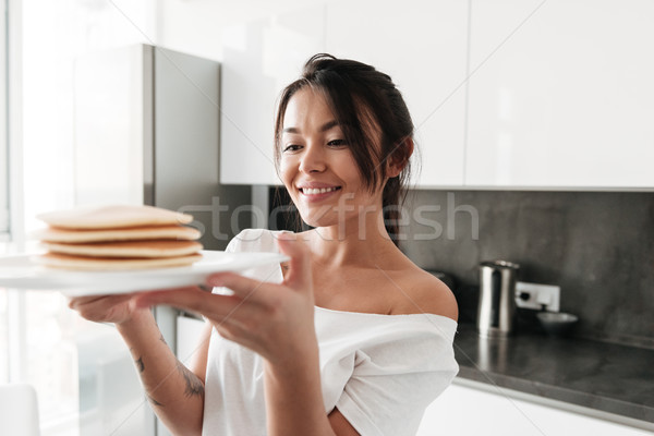 Cheerful young woman holding pancakes. Stock photo © deandrobot