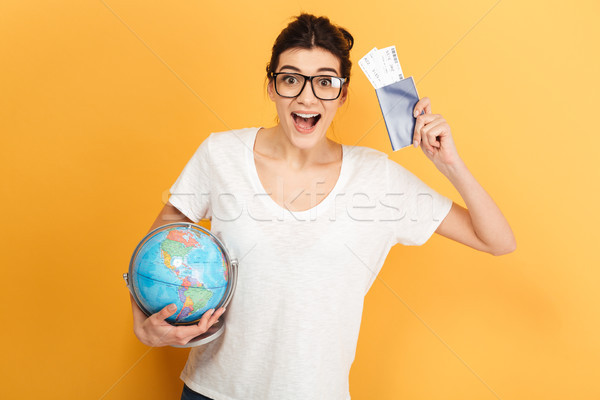 Excited surprised woman wearing glasses holding globe and passport with tickets. Stock photo © deandrobot