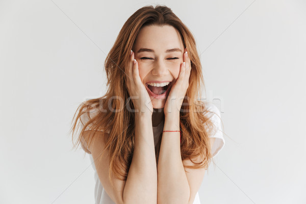 Laughing woman in t-shirt holding cheeks with closed eyes Stock photo © deandrobot