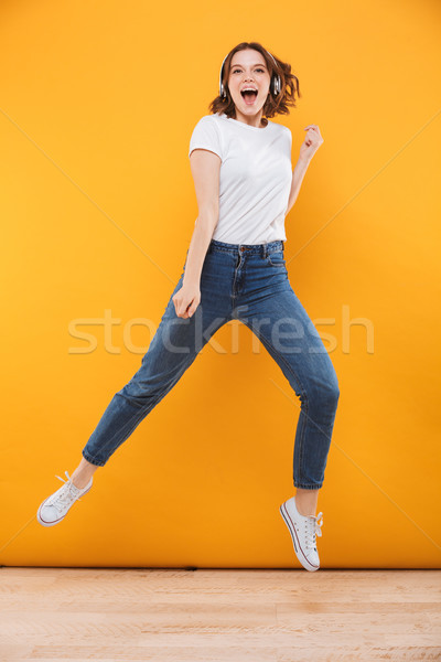 Emotional funny young woman jumping listening music. Stock photo © deandrobot