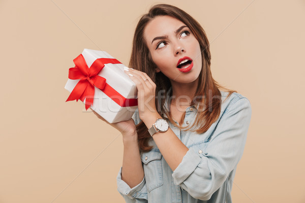 Portrait of a wondering young girl holding present box Stock photo © deandrobot