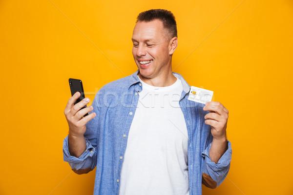 Portré elégedett középkorú férfi néz mobiltelefon tart Stock fotó © deandrobot
