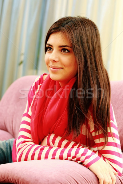 Young happy thoughtful woman sitting on the coach at home Stock photo © deandrobot
