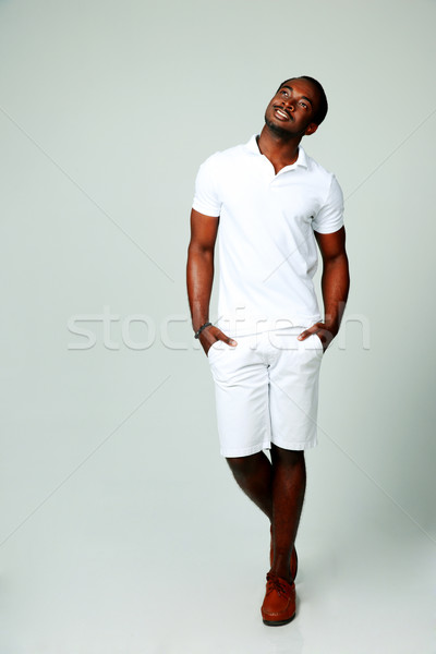 Full length portrait of a happy thoughtful african man on gray background Stock photo © deandrobot