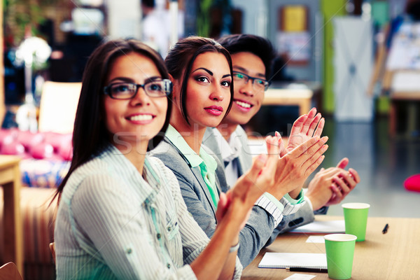 Happy business people applauding in a meeting. Business concept. Stock photo © deandrobot