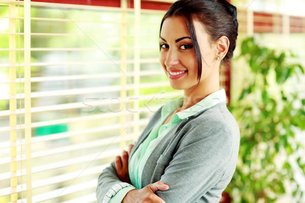 Portret glimlachend zakenvrouw armen gevouwen permanente Stockfoto © deandrobot