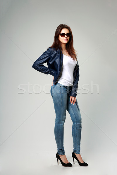 Full-length portrait of a young model in leather jacket and sunglasses on gray background Stock photo © deandrobot