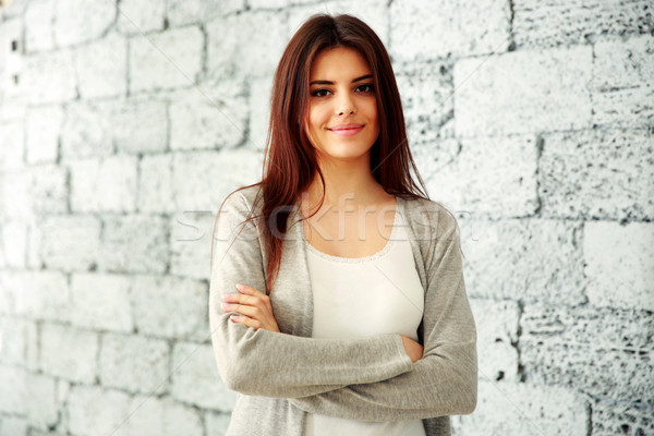 Young happy woman with arms folded standing near brick wall Stock photo © deandrobot