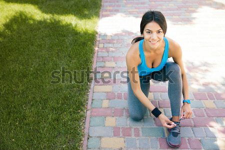 Happy woman tying her shoelace and looking at camera Stock photo © deandrobot
