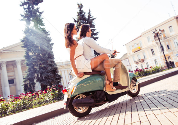 Young couple riding a scooter Stock photo © deandrobot