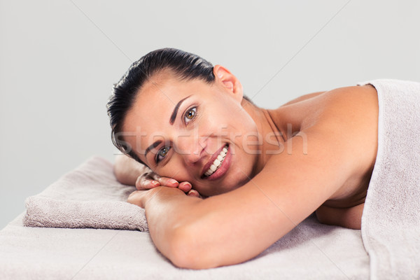 Happy cute woman lying on massage lounger Stock photo © deandrobot
