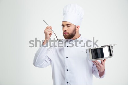 Handsome male chef cook tasting food Stock photo © deandrobot