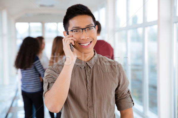 Happy male student talking on the phone Stock photo © deandrobot