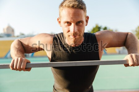 Male bodybuilder workout on parallel bars Stock photo © deandrobot