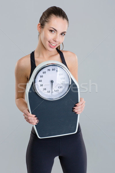Portrait of happy fitness girl in sportwear with weigh scale  Stock photo © deandrobot