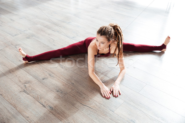 Attractive woman doing split on the floor Stock photo © deandrobot