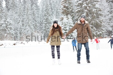 Portret uśmiechnięty para łyżwiarstwo odkryty śniegu Zdjęcia stock © deandrobot