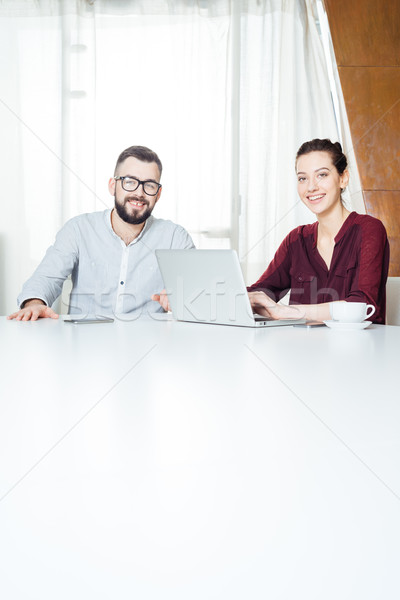 Two smiling businesspeople sitting and using laptop in meeting room Stock photo © deandrobot