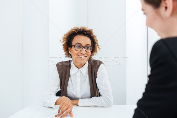 Cheerful african american businesswoman interviewing candidate for new position  Stock photo © deandrobot