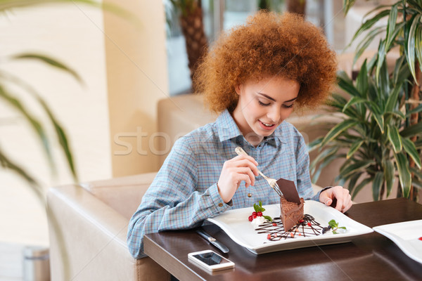 Cute curly young woman eating dessert in cafe Stock photo © deandrobot