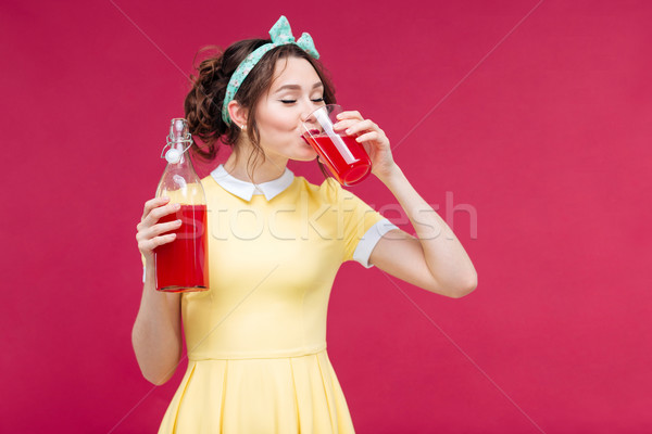 Cute lovely young woman in yellow dress drinking juice Stock photo © deandrobot