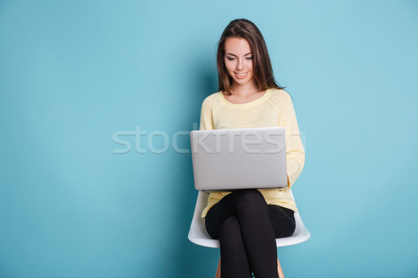 Smart beautiful young girl using laptop over blue background Stock photo © deandrobot