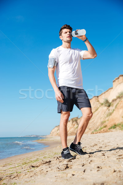 Stock photo: Sportsman standing and drinking water on the beach