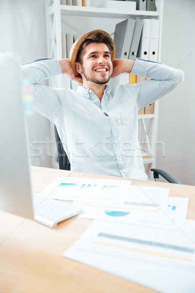 Cheerful young man in hat sitting and relaxing in office Stock photo © deandrobot
