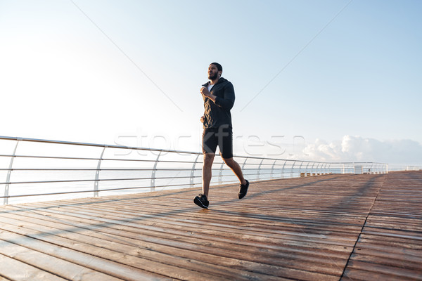 Sportsman listening to music and running on pier at sunset Stock photo © deandrobot