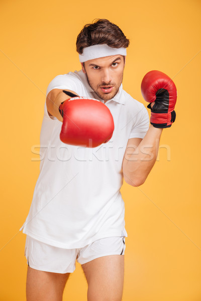 Handsome young man boxer in red gloves standing and boxing Stock photo © deandrobot