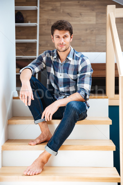 Portrait of a young handsome man sitting on the staircase Stock photo © deandrobot