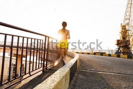 Attractive fit man running along bridge at sunset light Stock photo © deandrobot
