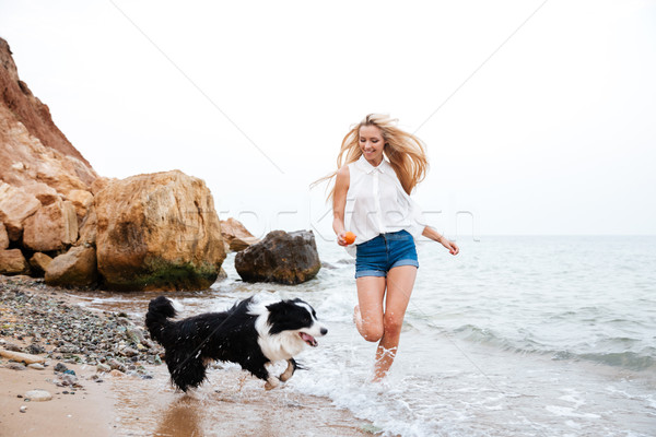 Young smiling girl running with her dog on the beach Stock photo © deandrobot