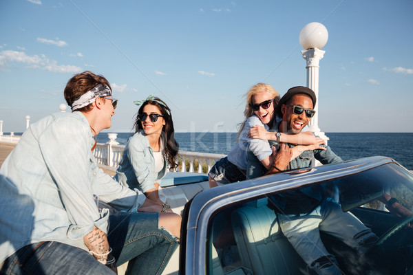 Multiethnic group of people talking and having fun in cabriolet Stock photo © deandrobot
