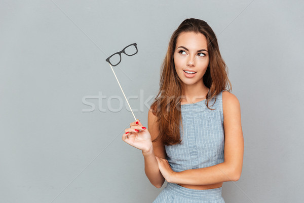 Stock photo: Pensive young woman with glasses props standing and thinking