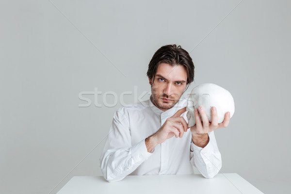 Man sitting and pointing finger at fake skull in hands Stock photo © deandrobot