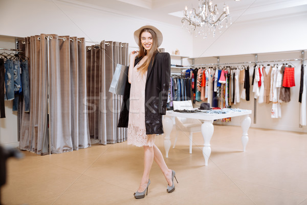 Cheerful woman with shopping bags standing in showroom Stock photo © deandrobot