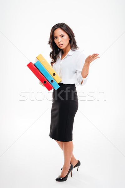 Serious smart asian businesswoman holding binders waving hand Stock photo © deandrobot