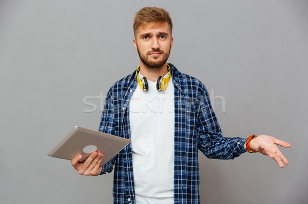 Portrait of amazed frustrated man using tablet computer Stock photo © deandrobot