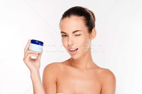 Smiling young woman holding cream bottle and winking Stock photo © deandrobot
