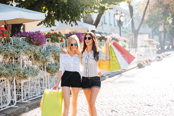Happy young women with shopping bags walking along city street Stock photo © deandrobot