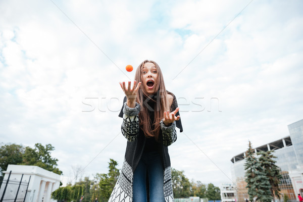 Surprised woman standing and playing with dog outdoors Stock photo © deandrobot