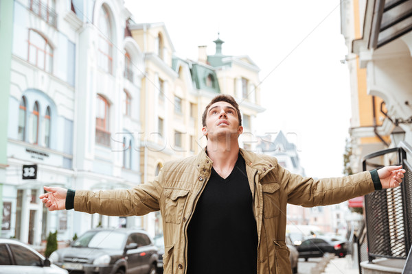 Handsome young man walking on the street and looking up Stock photo © deandrobot