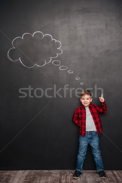 Child thinking with thought bubble on chalkboard while pointing up Stock photo © deandrobot